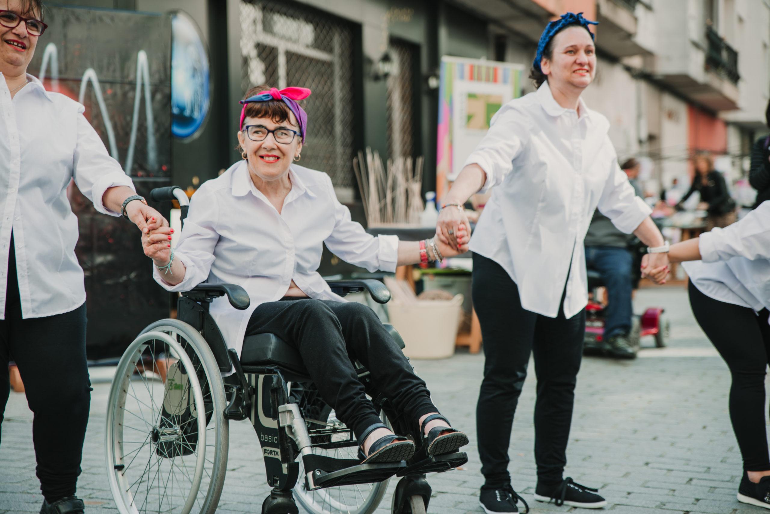 Angy na cadeira de rodas dándose a man cas súas compañeiras de artes escénicas