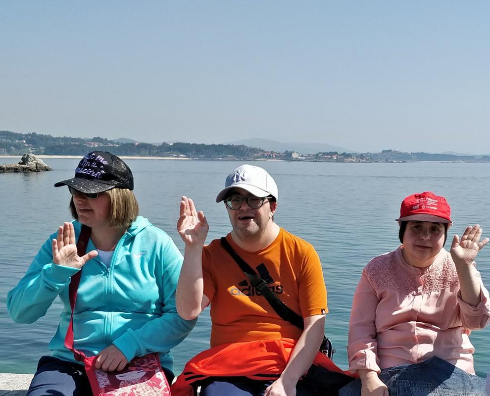 Mónica, Ramón e Elena no paseo do Touro en Ribeira co mar de fondo nunha actividade de ocio na comunidade