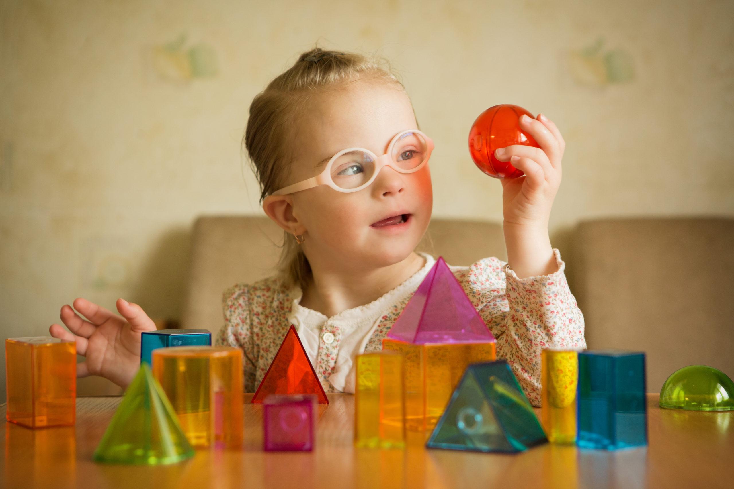 Nena con síndrome de Down tocando e observando materiais con formas xeométricas para traballar a estimulación óculo manual