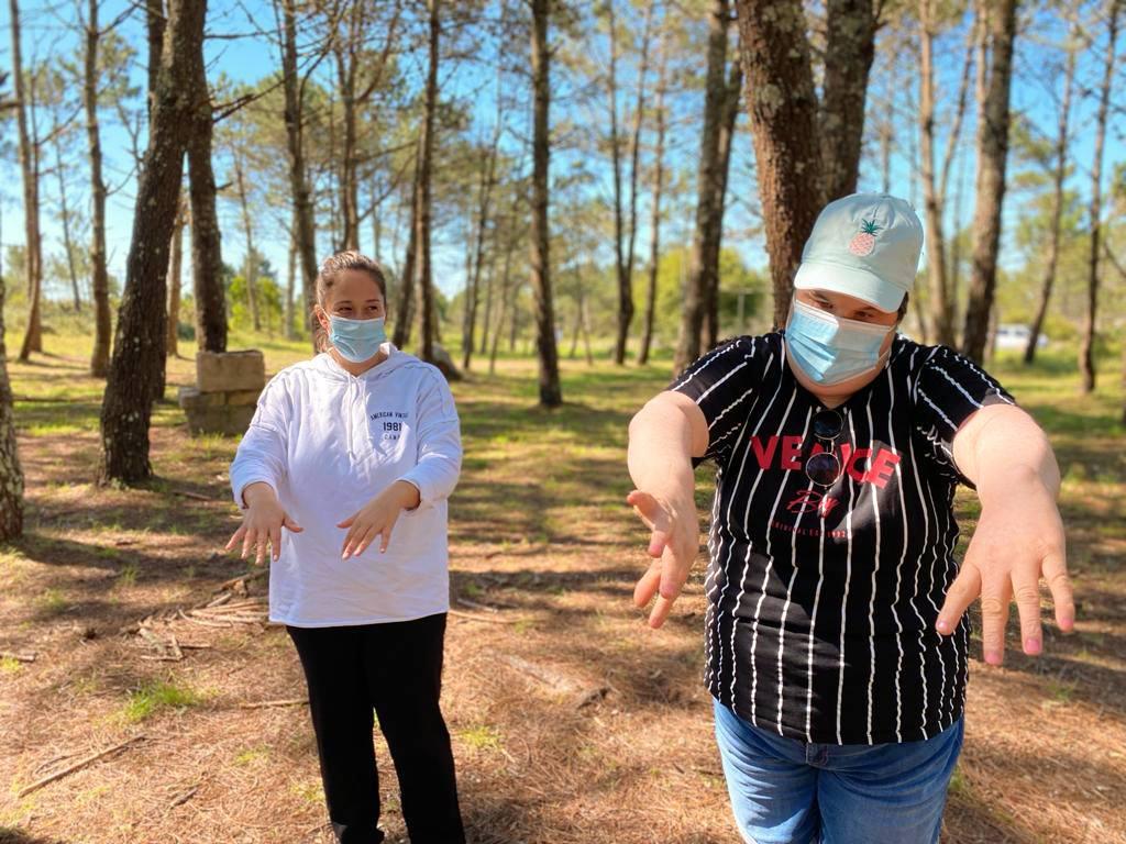 Paula, voluntaria de Ambar realizando unha actividade na natureza con algunhas persoas usuarias de Ambar