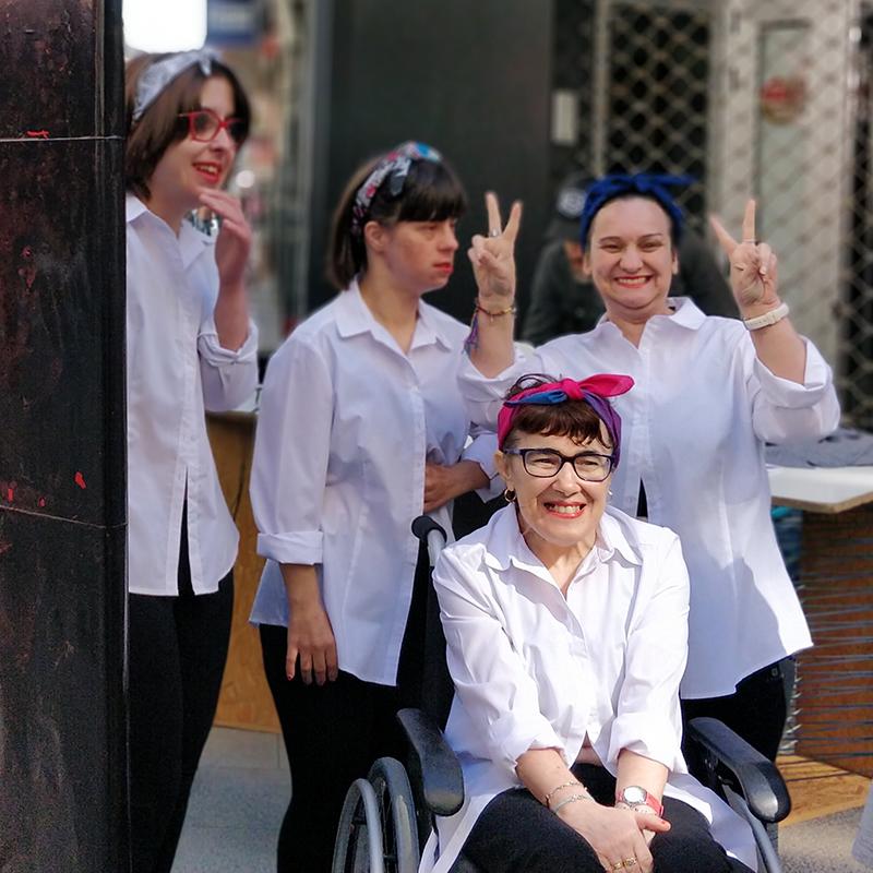 Grupo de artes escénicas con una persona con movilidad reducida esperando para salir a actuar en en el centro de Boiro